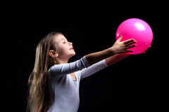 Emotional rhythmic gymnast dancing with ball. Emotional little rhythmic gymnast dancing with ball stock photo