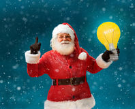Emotional Santa Claus showing cartoon bulb - having good idea!. Smiling Santa Claus on blue background. Merry Christmas & New Year's Eve concept Royalty Free Stock Photography