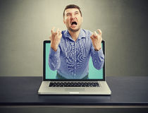 Emotional screaming man got out of the laptop Stock Photos