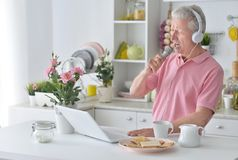 Emotional senior man singing karaoke. With laptop at home Stock Images