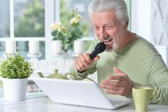 Emotional senior man singing karaoke. With laptop at home Royalty Free Stock Images