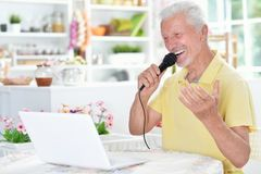 Emotional senior man singing karaoke with tablet. At home Stock Photo
