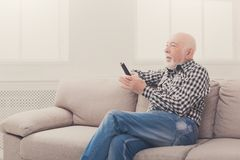 Emotional senior man watching tv copy space. Emotional senior man watching tv, sitting on couch with remote controller, copy space Royalty Free Stock Photos