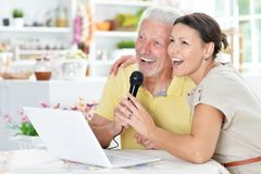 Senior man singing karaoke. Emotional senior men with adult daughter singing karaoke with laptop at home Stock Photo