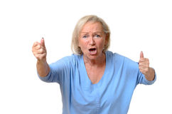 Emotional senior woman with clenched fists Stock Images