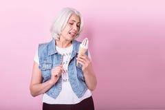 Emotional senior woman holding an icecream. Stock Images