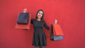 Emotional shopper woman rejoices at new purchases on black Friday seasonal sale. On background red wall stock video