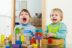 Emotional siblings playing with toy blocks Royalty Free Stock Photography