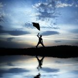 Emotional silhouette. Photo of a woman... throw in air a blancket over a lake Royalty Free Stock Photos