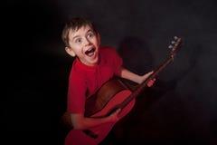 Emotionaler Junge mit Akustikgitarre lizenzfreie stockfotografie