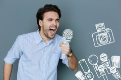 Enthusiastic singer holding a microphone and singing loudly. Emotional singer. Excited young man standing with a big microphone and singing loudly Royalty Free Stock Photography