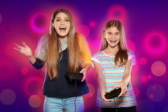 Emotional sisters playing video games. On color background stock photography