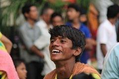 Emotional smile expression of a poor street man. A young man laugh heartily showing his white teeth and happy on the streets of Mumbai. India royalty free stock photos