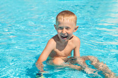 Emotional smiling little boy sitting into the pool Stock Photo