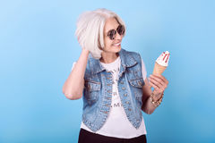 Emotional smiling senior woman holding an icecream. Royalty Free Stock Image