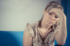 Emotional Stress, Headache, Woman at home on the sofa Stock Image