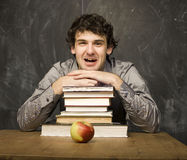 Emotional student with the books and red apple in class room, at blackboard. The young emotional student with the books and red apple in class room, at Royalty Free Stock Image