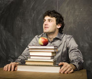Emotional student with the books and red apple in class room, at blackboard. The young emotional student with the books and red apple in class room, at Stock Photo