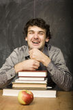 Emotional student with the books and red apple in class room, at blackboard Stock Images
