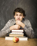 Emotional student with the books and red apple in class room, at blackboard. The young emotional student with the books and red apple in class room, at Royalty Free Stock Photography