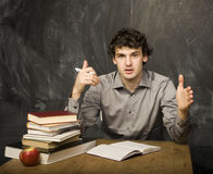 Emotional student with the books and red apple in class room, at blackboard. The young emotional student with the books and red apple in class room, at Stock Image