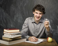 Emotional student with the books and red apple in class room, at blackboard. The young emotional student with the books and red apple in class room, at Royalty Free Stock Photo