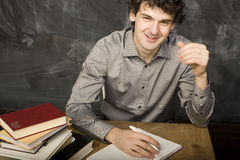 Emotional student with the books and red apple in class room, at blackboard Stock Photo