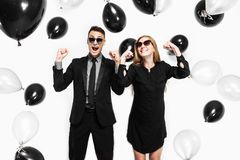 Emotional stylish couple, a man in a suit and a girl in a dress, in his hands, balloons and bags, for shopping, rejoice, waiting stock photo