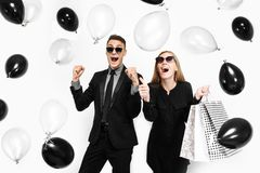 Emotional stylish couple, a man in a suit and a girl in a dress, in his hands, balloons and bags, for shopping, rejoice, waiting royalty free stock images