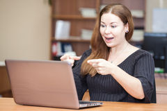 Emotional successful woman pointing at laptop Stock Image