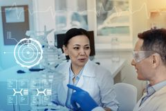 Clever colleagues talking while sitting in their modern laboratory. Emotional talk. Emotional friendly scientist feeling glad while sitting in their modern Stock Image