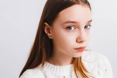 Emotional teen girl in a white knitted sweater on a light gray background.Space for text. Emotional teen girl in a white knitted sweater on a light gray stock image