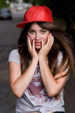 Emotional teen model. Beautiful emotional teen model on street. red cap, grey t-shirt, dark blue shorts Stock Images