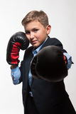 Emotional teenager blond boy in a suit with boxing gloves in hands Royalty Free Stock Photos