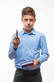 Emotional teenager boy brunette in a blue shirt with a diary and a pen in hand Stock Image