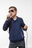 Emotional teenager boy brunette in sunglasses with a microphone royalty free stock images