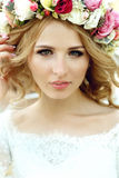 Emotional touched beautiful blonde bride in white dress in wreat Royalty Free Stock Photography