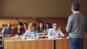 Emotional tutor is speaking to adult students explaining new information while attentive pupils are listening and taking. Notes. Profession, higher education stock footage