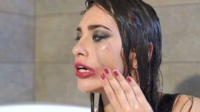 Girl washes makeup in shower under water, her red lipstick smeared on the face. Emotional upset girl in the shower, she has bright makeup. Water runs down her stock video