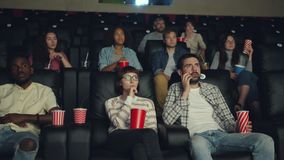 Emotional viewers enjoying scary thriller in cinema watching film with attention. Emotional viewers attractive young people are enjoying scary thriller in cinema stock video footage