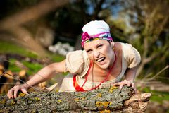 Emotional wild girl creeps along the grass. And growls, anger emotion Stock Photography