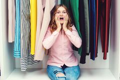 Emotional woman choosing her fashion outfit. Shopping girl think. Ing what to wear in front of many choices of clothes. Pretty woman sitting among clothes in royalty free stock photo