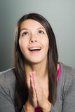 Emotional woman clasping her hands in supplication Royalty Free Stock Photos