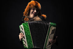 Emotional woman in fur hat playing the accordion Royalty Free Stock Photo