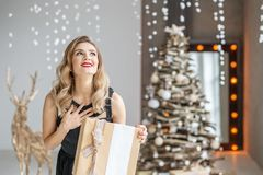 Emotional woman gets a valuable gift surprise. The girl in a bla. Ck dress is rejoicing. Concept of Happy Christmas and New Year, winter, party Royalty Free Stock Photos