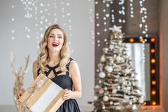 An emotional woman got a surprise gift box. The girl in black dr. Ess. Concept of Happy Christmas and New Year, winter, party Royalty Free Stock Photo