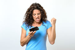 Emotional woman holding a broken mobile phone. Reacting in anguish or frustration with closed eyes and open mouth stock photos