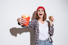 Emotional woman holding fries and burger Royalty Free Stock Image