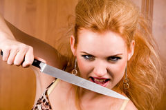 Emotional woman with kitchen knife Royalty Free Stock Image
