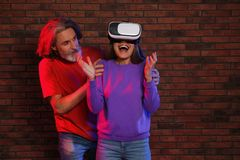 Emotional woman playing video games with VR headset and mature man near wall royalty free stock photos